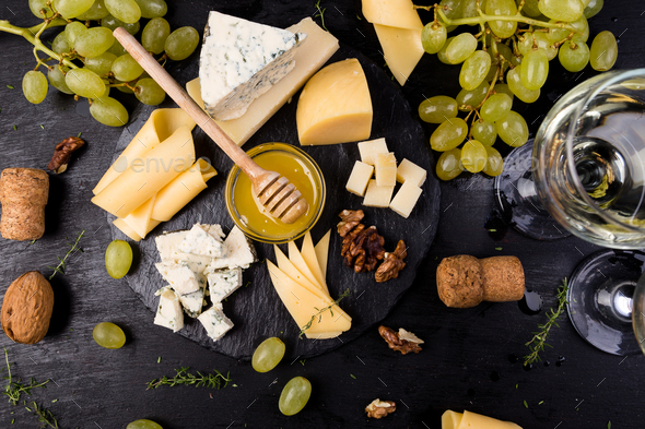 Cheese plate. Assortment of cheese with walnuts, bread an honey on stone slate plate. - Stock Photo - Images