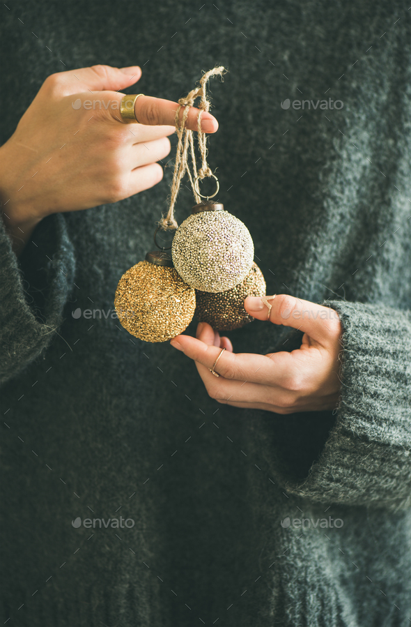 Woman in grey sweater holding decorative golden balls in hands - Stock Photo - Images