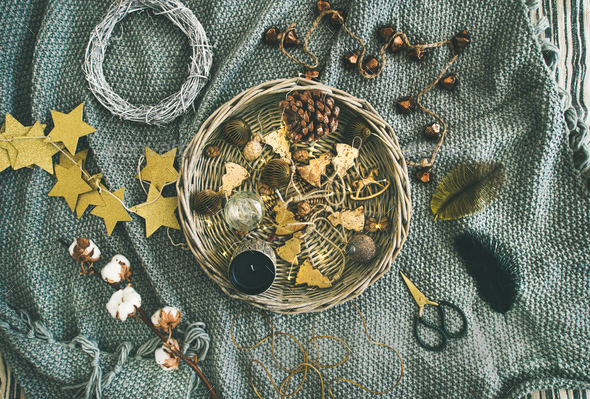 Flat-lay of Christmas toys, garlands, lights, wreath over grey blanket - Stock Photo - Images
