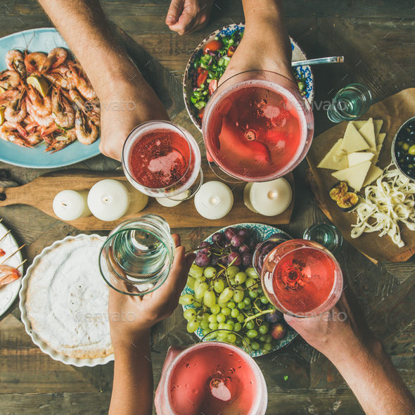 Flat-lay of friends hands eating and drinking together, square crop - Stock Photo - Images