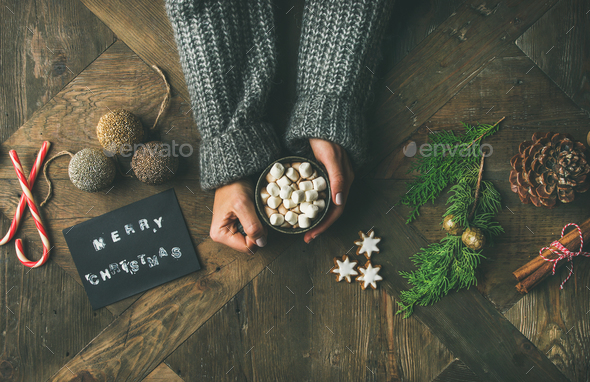 Flat-lay of greeting card, woman's hands in sweater holding mug - Stock Photo - Images