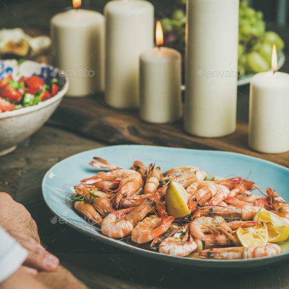Salad, shrimps and candles on wooden table, square crop - Stock Photo - Images