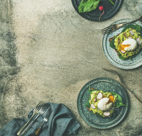 Healthy vegetarian wholegrain avocado toasts with poached egg, copy space - Stock Photo - Images