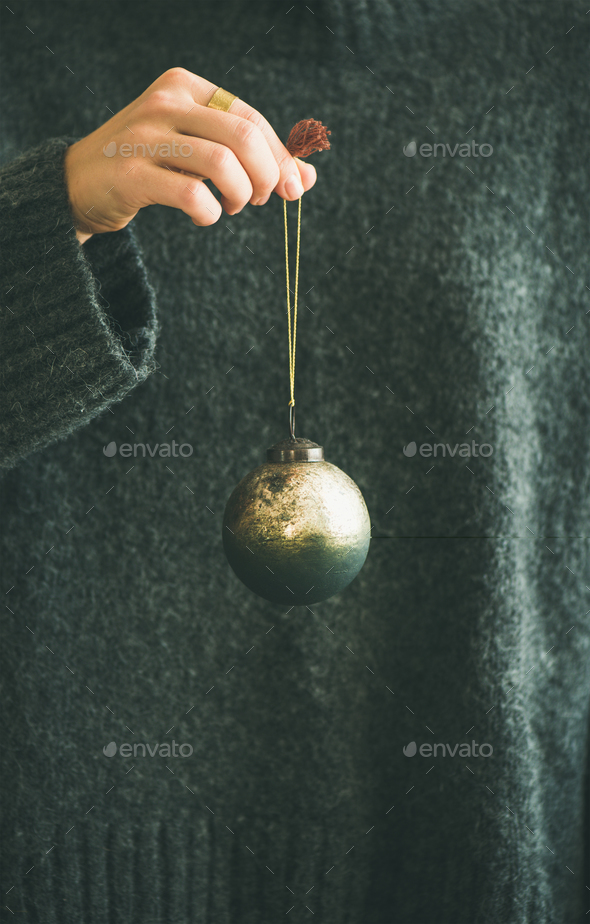 Woman in grey sweater holding decorative golden ball in hand - Stock Photo - Images