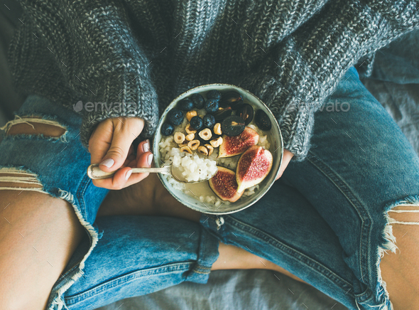 Woman in shabby jeans and sweater eating healthy breakfast - Stock Photo - Images