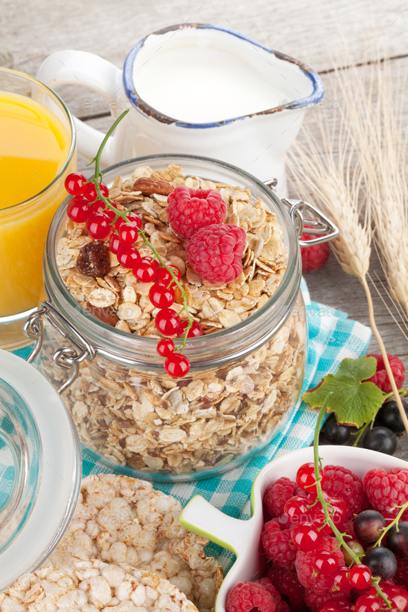 Healthy breakfast with muesli, berries, orange juice and milk - Stock Photo - Images