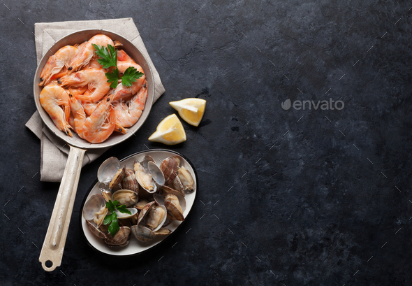 Fresh seafood on stone table. Scallops and shrimps - Stock Photo - Images