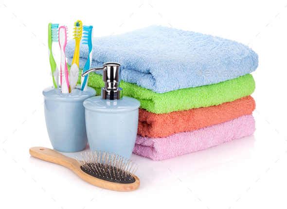 Four toothbrushes, liquid soap, hairbrush and colorful towels - Stock Photo - Images