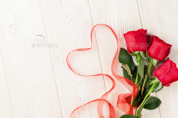 Red roses and heart shape ribbon over wood - Stock Photo - Images