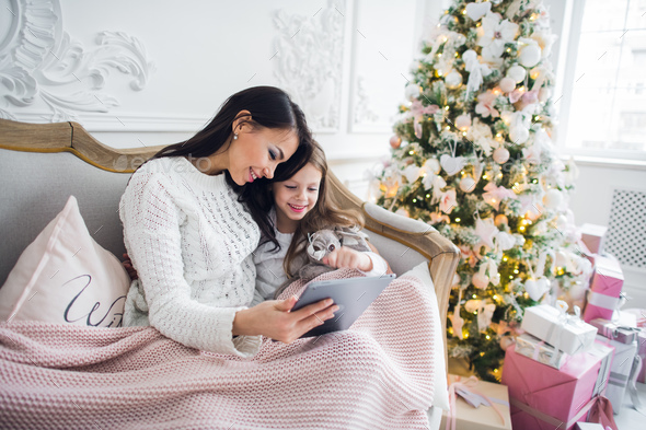 Beautiful young woman and her daughter with the tablet at Christmas time. Close-up. - Stock Photo - Images