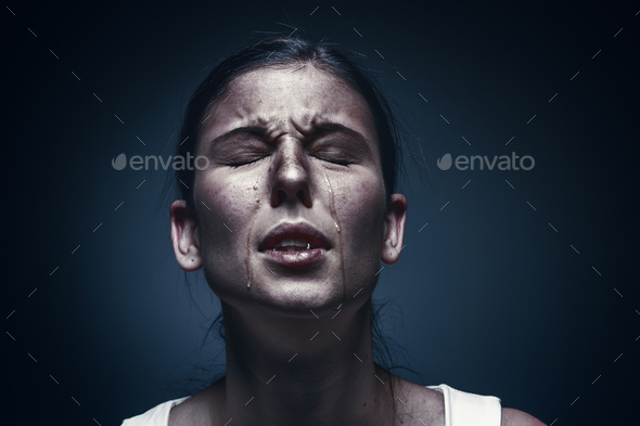 Close up portrait of a crying woman with bruised skin and black eyes - Stock Photo - Images