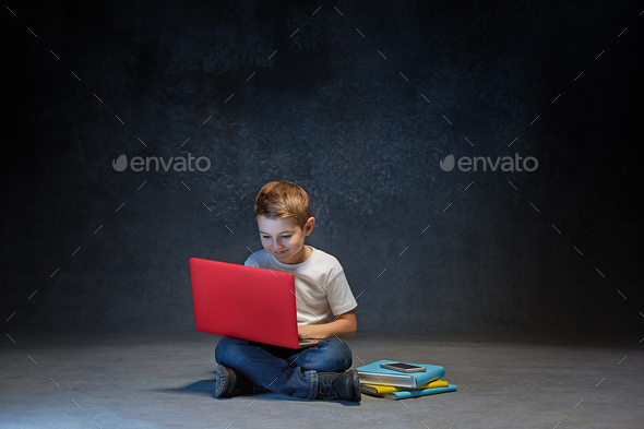 Little boy sitting with laptop in studio - Stock Photo - Images