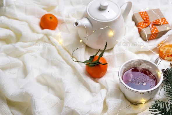Hot Cup of tea with tangerines and sweaters on bed - Stock Photo - Images