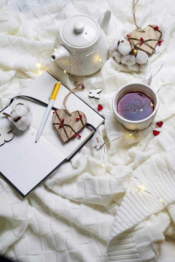 Warm knitted plaid,cup of hot tea and notebook - Stock Photo - Images