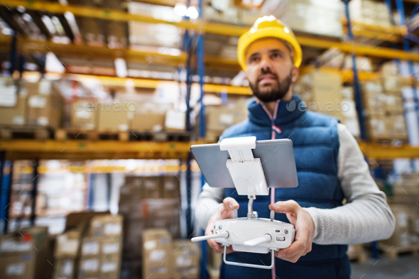 Man with tablet and drone controller in a warehouse. - Stock Photo - Images