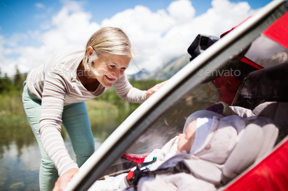 Senior woman and grandchildren in jogging stroller. - Stock Photo - Images