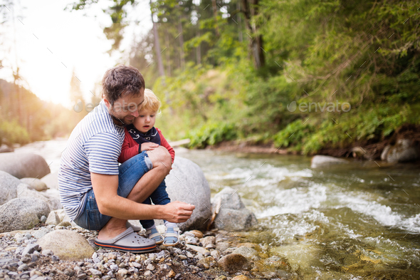 Young father with little boy at the river, summer day. - Stock Photo - Images