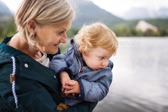Senior woman with little boy at the lake. - Stock Photo - Images