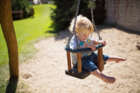 Little boy on the swing at the playground. - Stock Photo - Images