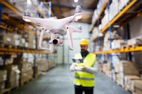 Man with drone in a warehouse. - Stock Photo - Images