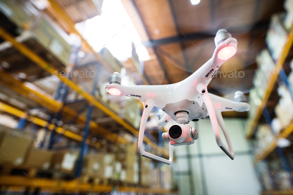 White drone flying inside the warehouse. - Stock Photo - Images