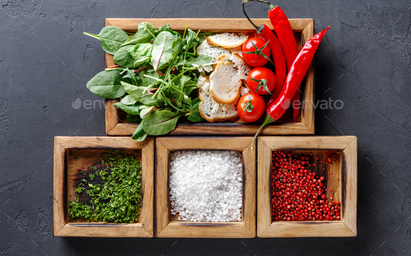 Woman holding cooking ingredients and herbs in wooden box on dark background - Stock Photo - Images