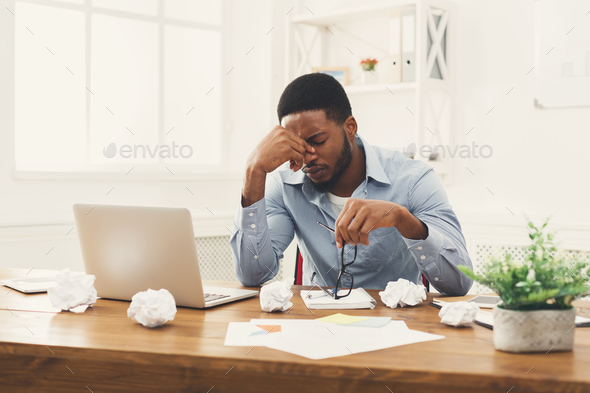 Overworking african-american employee at workplace - Stock Photo - Images