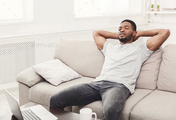 Handsome young african-american man relaxing on the couch at home - Stock Photo - Images