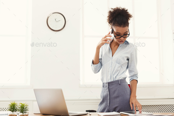 Business woman with mobile phone standing at office - Stock Photo - Images