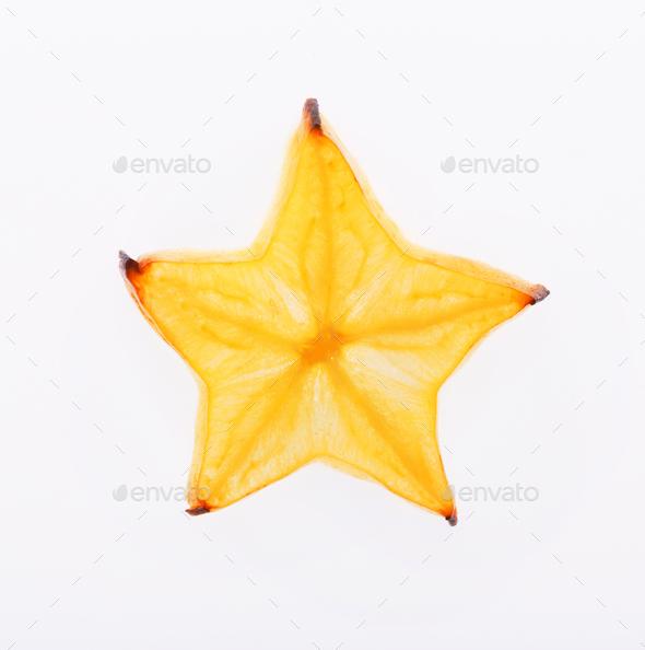 Yellow star fruit slice backlit, isolated on white - Stock Photo - Images