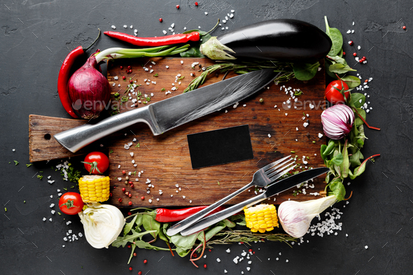 Wooden desk with vegetables border on dark background - Stock Photo - Images