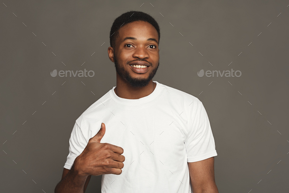 Happy black man showing thumb up gesture, studio shot - Stock Photo - Images