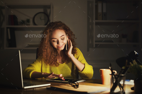 Smiling woman at work talking on phone - Stock Photo - Images