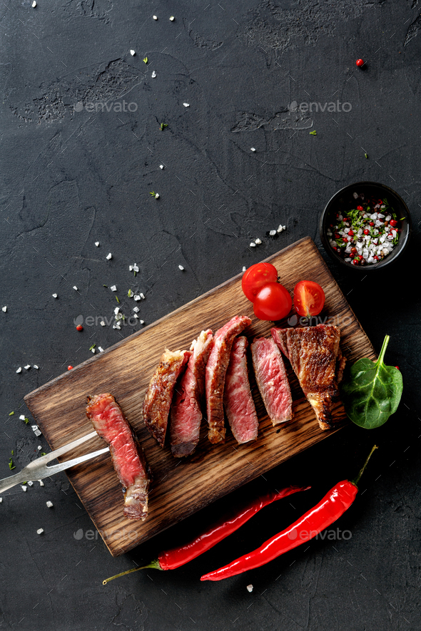 Rib eye steaks and spices on wood at black background - Stock Photo - Images