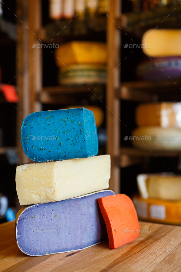 Gouda pesto cheese assortment. Lavender, blue, violet and red at grocery shop background - Stock Photo - Images