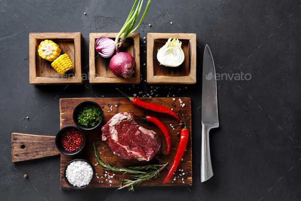 Rib eye steak with spices on wooden desk and diverse cooking ingredients in wooden boxes. - Stock Photo - Images
