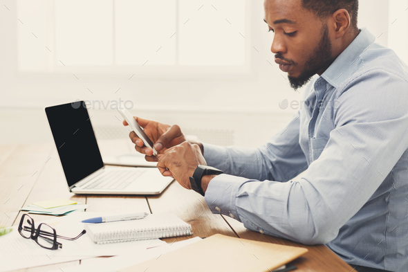 Young black businessman with smartwatch in office - Stock Photo - Images