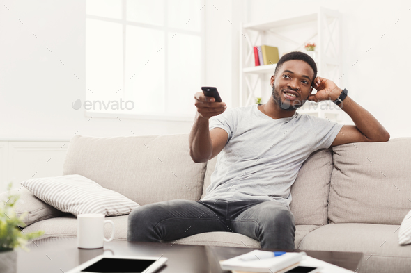 Young man watching tv using remote controller in living room - Stock Photo - Images