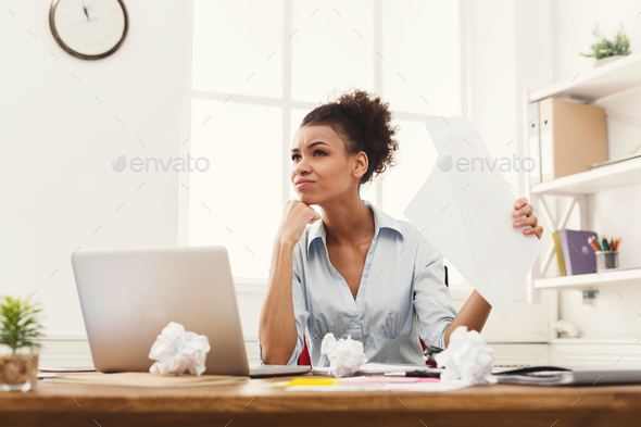 Angry business woman reading document at office desktop - Stock Photo - Images