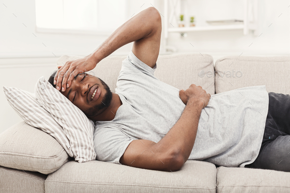 Handsome young african-american man suffering from stomachache and headache - Stock Photo - Images
