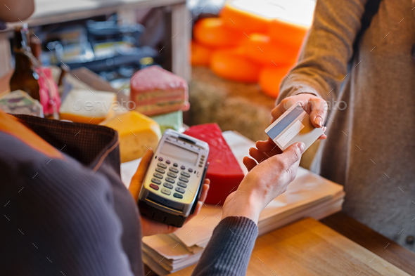 Customer paying for order of cheese in grocery shop. - Stock Photo - Images