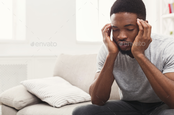 Young african-american man having headache at home - Stock Photo - Images