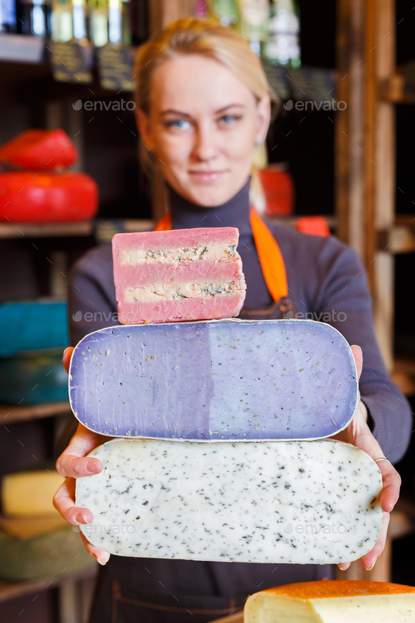 Large pieces of cheese in shop assistant hands - Stock Photo - Images