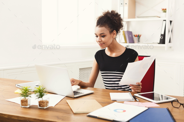 Business woman reading document at office desktop - Stock Photo - Images
