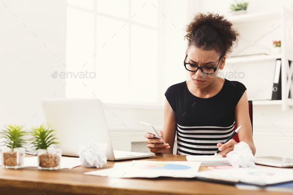 Serious woman making notes in office - Stock Photo - Images