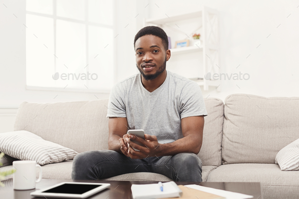 Smiling young man at home messaging on mobile - Stock Photo - Images