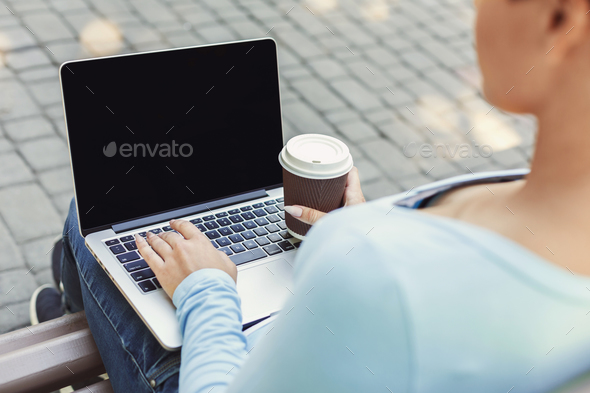 Female hands with laptop closeup,over shoulder shot outdoors - Stock Photo - Images