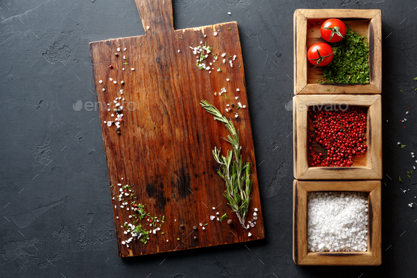 Wooden desk and diverse spices on dark background - Stock Photo - Images