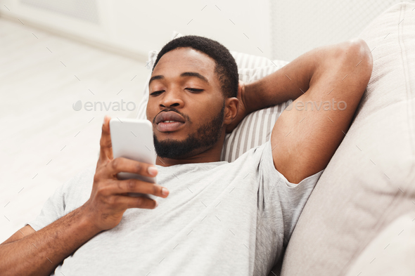Young man at home messaging on mobile - Stock Photo - Images