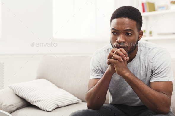 Disappointed young african-american man at home - Stock Photo - Images
